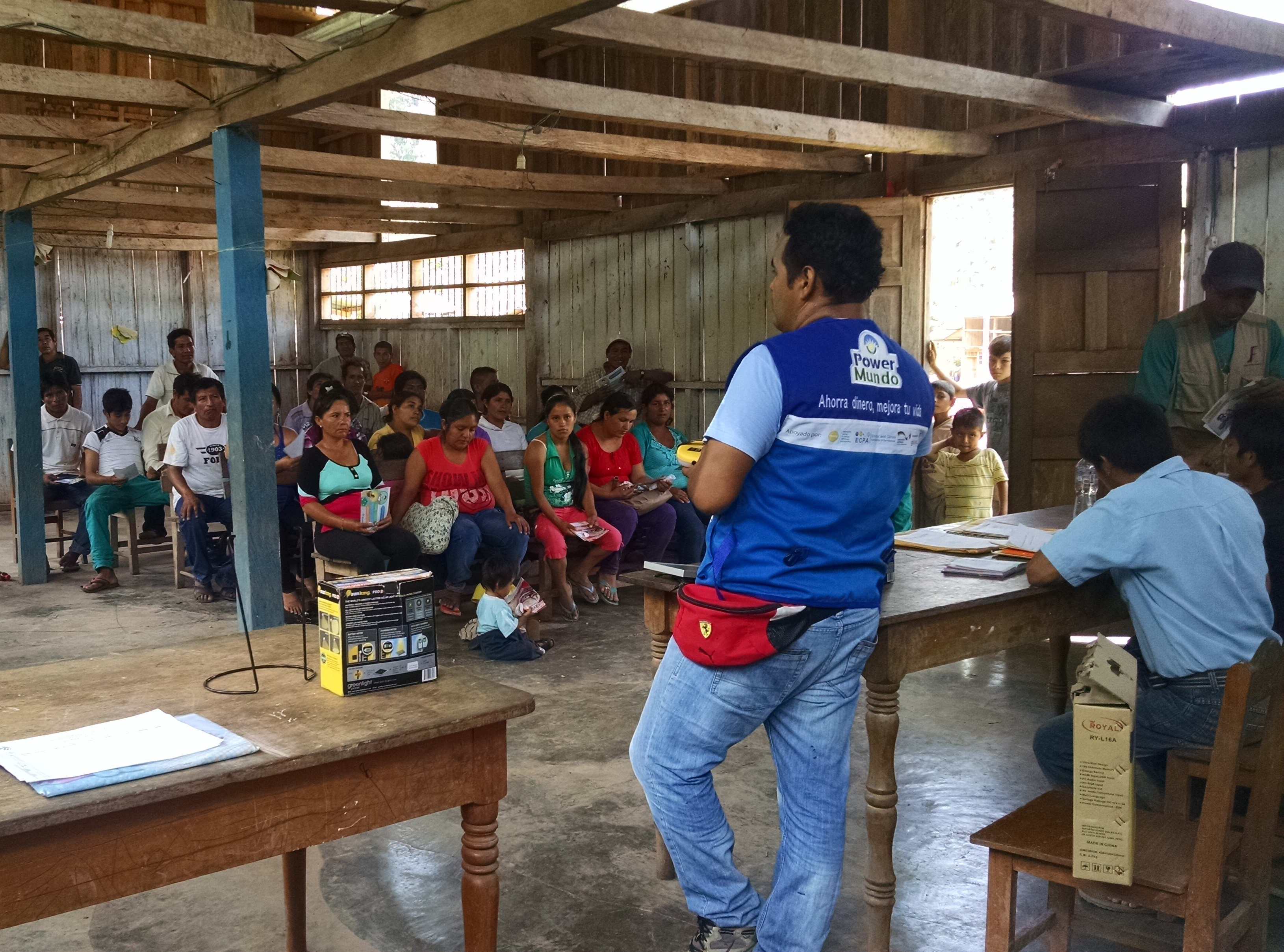 PowerMundo's Field Coordinator presenting the PAYG system at a community meeting in San Martín