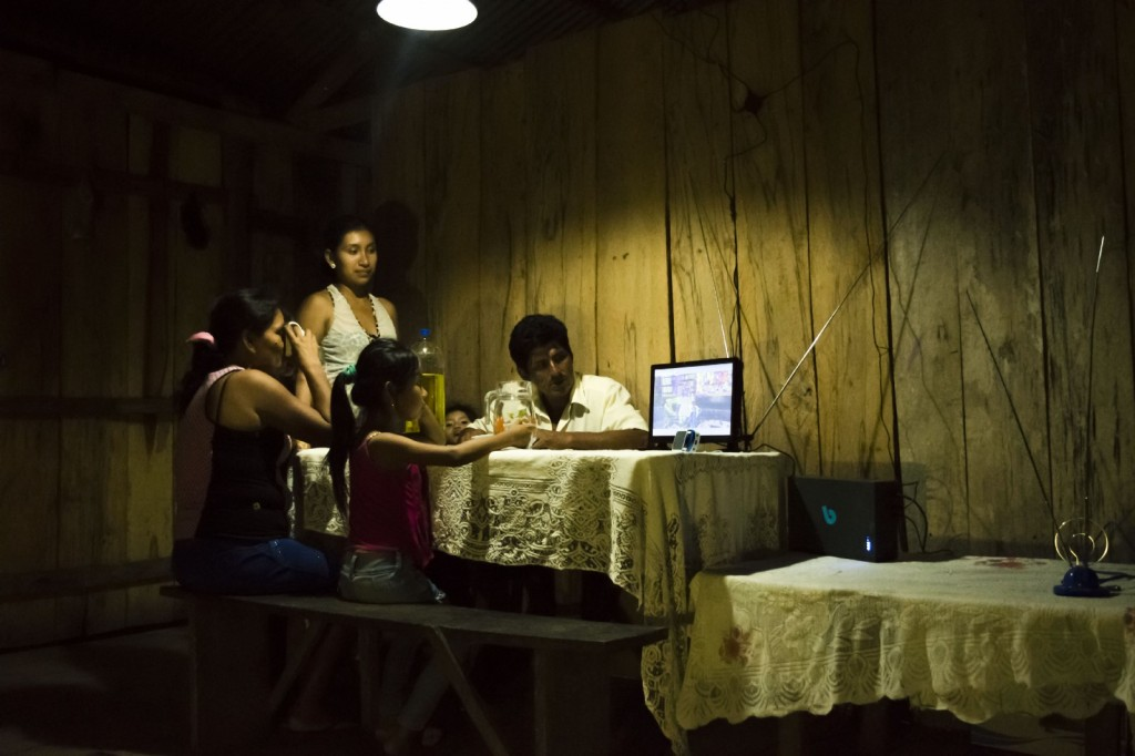A family in rural Iquitos watches the news on their new BBOXX solar-powered TV. Photo courtesy of PowerMundo.